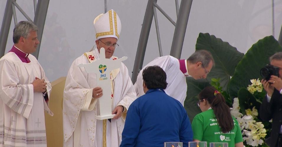 28.jul.2013 - Papa Francisco entrega cruz da JMJ (Jornada Mundial da Juventude) no fim da missa de encerramento da jornada, na praia de Copacabana, no Rio de Janeiro