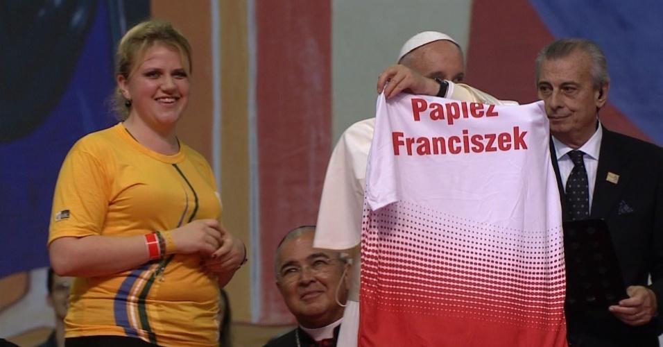 28.jul.2013 - Papa Francisco recebe camisa das mãos de jovem católica polonesa, durante encontro com voluntários da Jornada Mundial da Juventude, que acontece no Riocentro, no Rio de Janeiro. Próxima edição da jornada será realizada em Cracóvia, na Polônia, em 2016