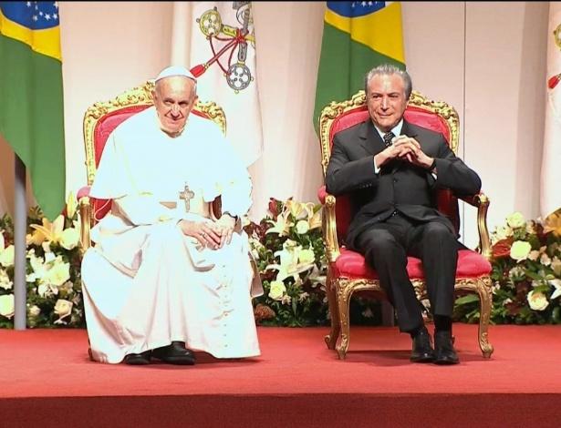 Papa Francisco senta ao lado do então vice-presidente Michel Temer durante sua visita ao Brasil, em 2013