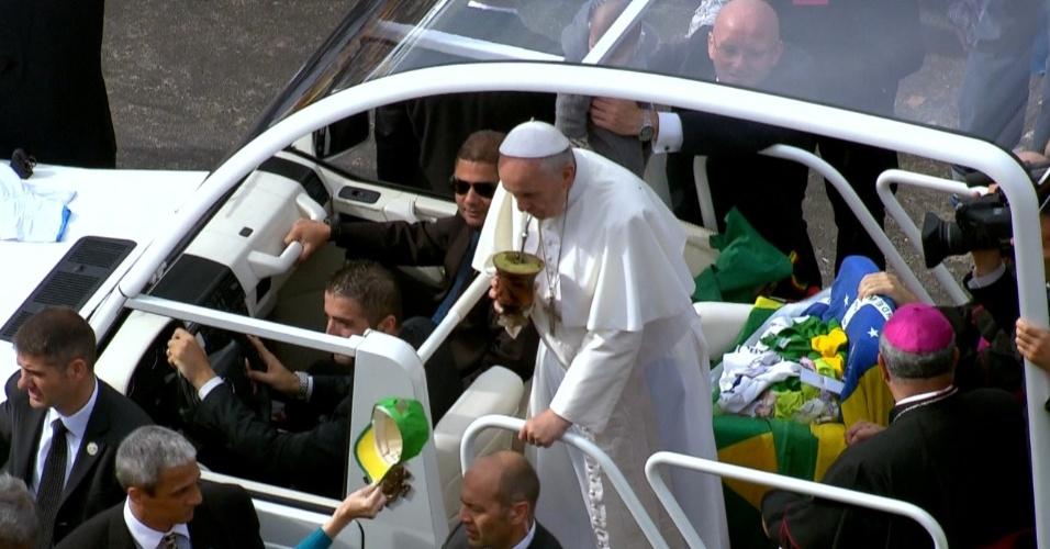 28.jul.2013 - Papa Francisco toma chimarrão oferecido por um fiel em seu papamóvel ao chegar à praia de Copacabana, no Rio de Janeiro, onde celebrará a missa de encerramento da JMJ (Jornada Mundial da Juventude)