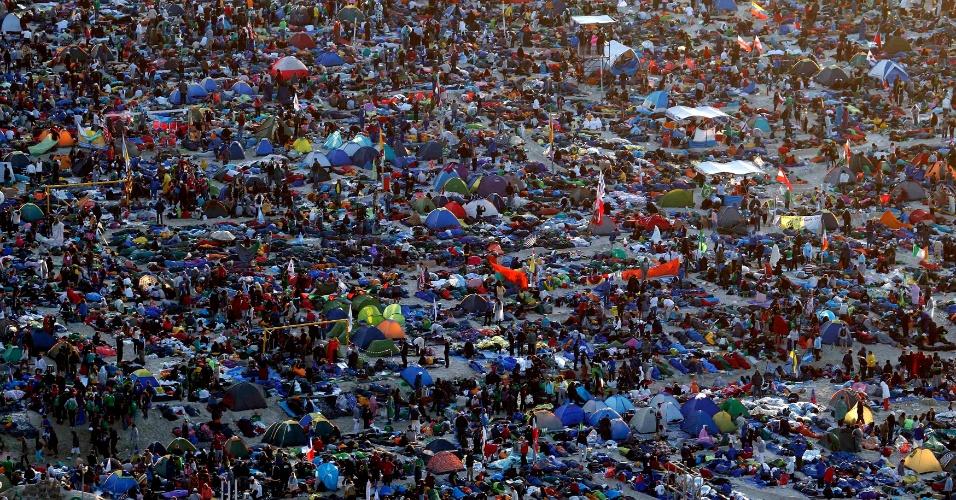 28.jul.2013 - Peregrinos aproveitam o nascer do sol na praia de Copacabana, onde, segundo organizadores, cerca de 3 milhões de pessoas passaram a noite em vigília, enquanto aguardam pela missa deste domingo (28) do papa Francisco, no último dia da Jornada Mundial da Juventude