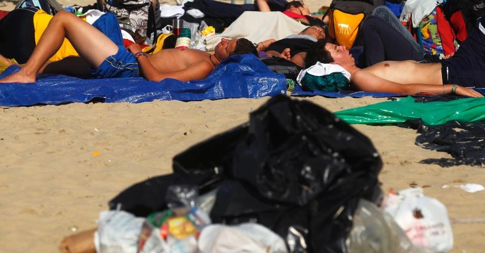 28.jul.2013 - Pessoas descansam próximas a sacos de lixo, na praia de Copacabana, na zona sul do Rio de Janeiro, neste domingo, após missa de encerramento da Jornada Mundial da Juventude