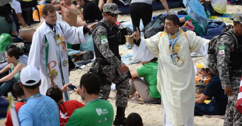 28.jul.2013 - Policial patrulha praia de Copacabana, no Rio de Janeiro, enquanto fiéis assistem celebração da missa do papa Francisco de encerramento da JMJ (Jornada Mundial da Juventude)