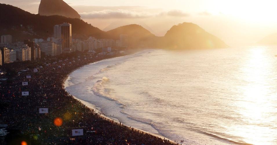 28.jul.2013 - Sol nasce enquanto peregrinos da Jornada Mundial da Juventude dormem na praia de Copacabana após vigília do papa Francisco, neste domingo (28), último dia do evento