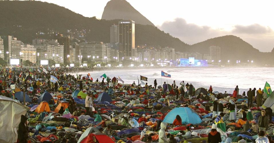 28.jul.2013 - Sol nasce enquanto peregrinos da Jornada Mundial da Juventude acordam após passarem a noite acampados na praia de Copacabana após vigília do papa Francisco, neste domingo (28), último dia do evento