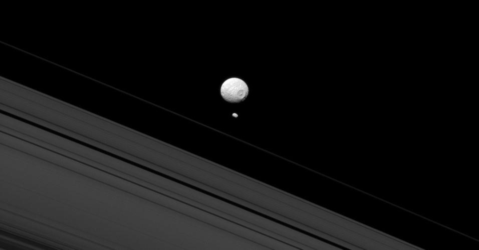 30.jul.2013 - Mimas e Pandora mostram como as luas de Saturno são excepcionais, ainda mais quando fotografadas juntas pela sonda Cassini. Segundo a Nasa (Agência Espacial Norte-Americana), o tamanho reduzido de Pandora mostra que ela não tem gravidade suficiente para ganhar uma formato mais arrendondado, como tem o seu colega maior, que tem 396 quilômetros de diâmetro. Para os astrônomos, o satélite alongado, com cerca de 81 quilômetros de comprimento, pode guardar pistas de como os corpos próximos aos anéis de Saturno se formaram