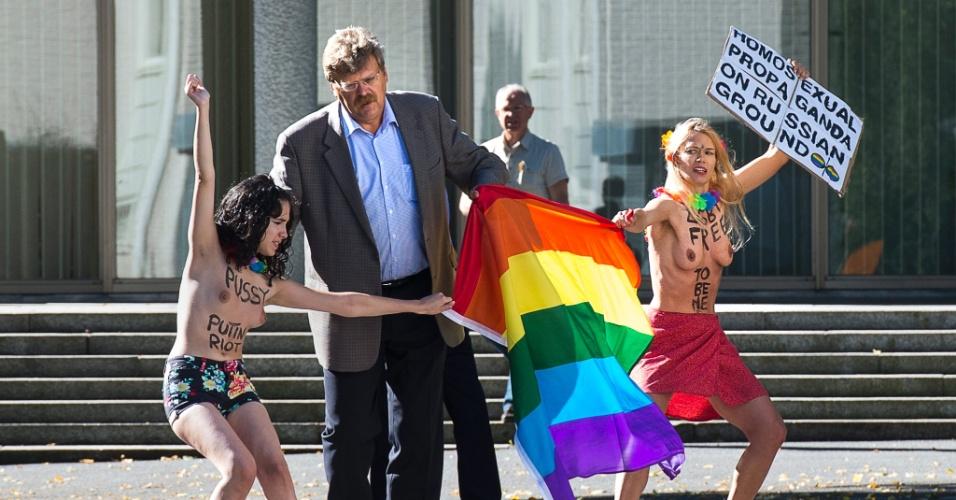 1º.ago.2013 - Homem tenta retirar faixa de bandeira que simboliza o movimento gay durante protesto de ativistas do grupo Femen em frente à Embaixada da Rússia em Estocolmo, na Suécia. As ativistas protestam contra um projeto de lei antigay do país e a estigmatização dos homossexuais