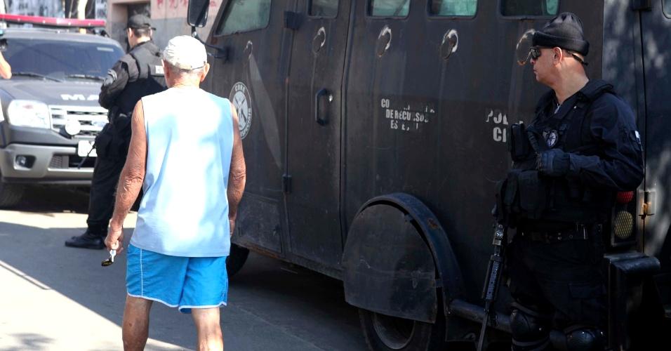 2.ago.2013 - Morador passa perto do caveirão do Bope (Batalhão de Operações Especiais) durante magaoperação conjunta para cumprir oito mandados de prisão no conjunto de favelas do Lins de Vasconcelos, na zona norte do Rio de Janeiro. Até as 10h30, quatro homens foram presos e um morreu em confronto com o Bope