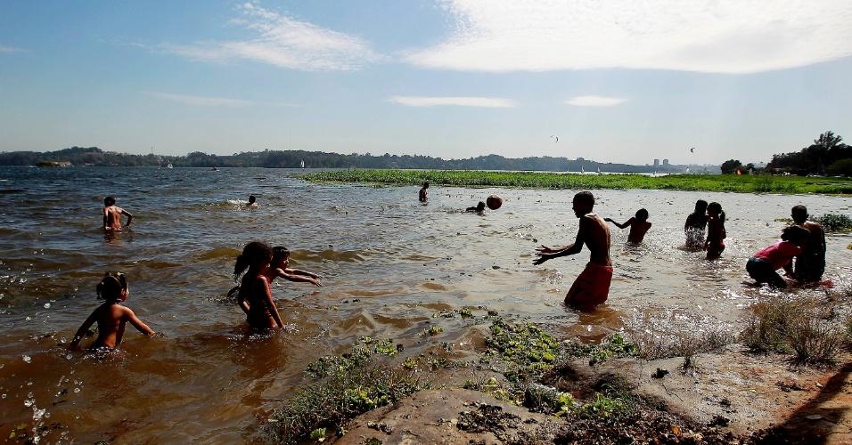 4.ago.2013 - Frequentadores da Prainha do Sol, na orla da represa Guarapiranga, zona Sul de São Paulo, se refrescam durante tarde de calor em pleno inverno
