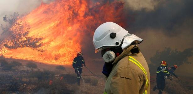 Bombeiros gregos correm para um terreno mais seguro, enquanto outro pede ajuda por rádio durante um incêndio florestal em Maratona - Yannis Behrakis/Reuters