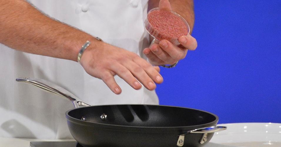 5.ago.2013 - Chef de cozinha Rich McGeown prepara o primeiro hambúrguer feito em laboratório durante conferência em Londres, na Inglaterra, nesta segunda-feira (5). Cientistas holandeses utilizaram células retiradas de uma vaca para reconstituir os músculos de carne bovina, que foram combinados a outros ingredientes para fazer o hambúrguer