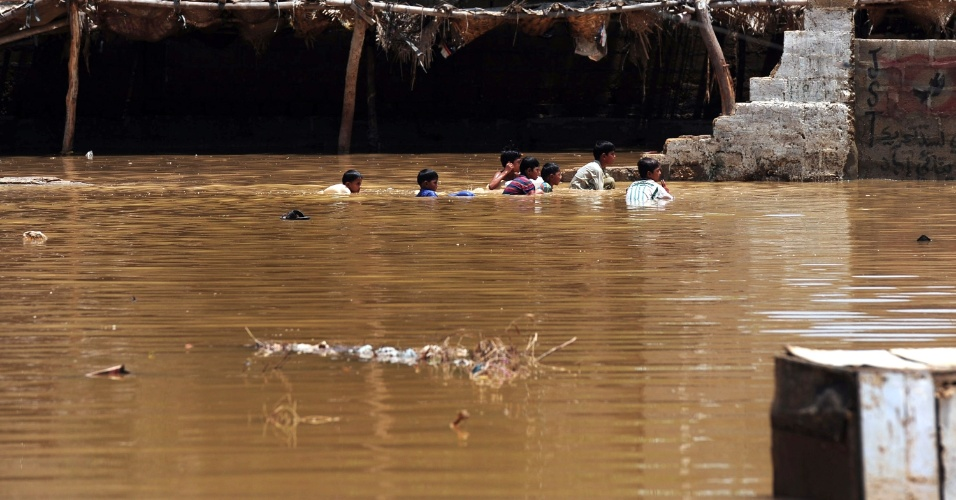 5.ago.2013 - Jovens paquistaneses nadam em região alagada após fortes chuvas de monção em Karachi, nesta segunda-feira (5)