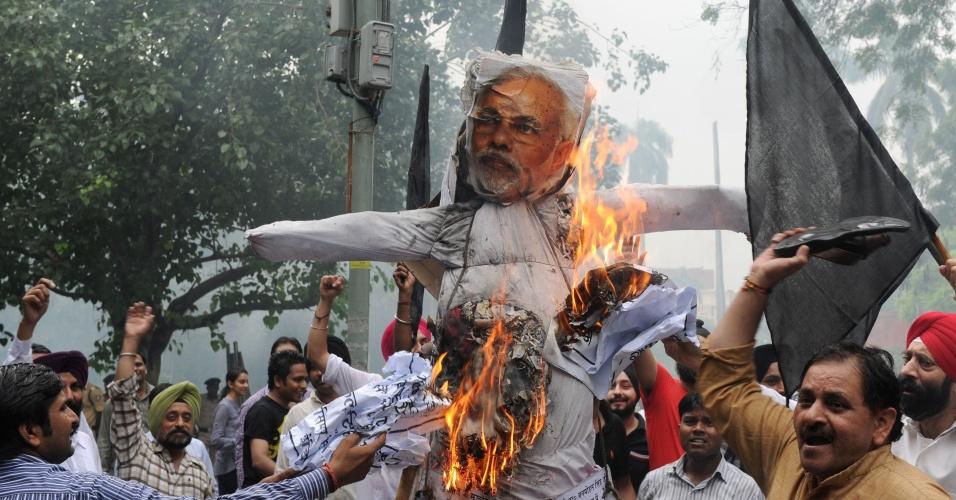 5.ago.2013 - Membros do fórum nacional da juventude indiana Sikh queimam boneco que representa o chefe do governo do Estado de Gujarat, Narendra Modi, durante protesto em Nova Déli, na Índia