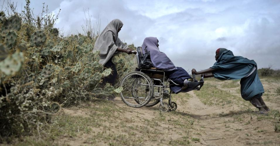 5.ago.2013 - Mulheres ajudam uma amiga de cadeira de rodas a atravessar por uma área de cactos em Afgoye, na Somália, no domingo (4). A Cruz Vermelha distribuiu alimentos como parte de um programa realizado junto às Nações Unidas durante o mês do Ramadã na região