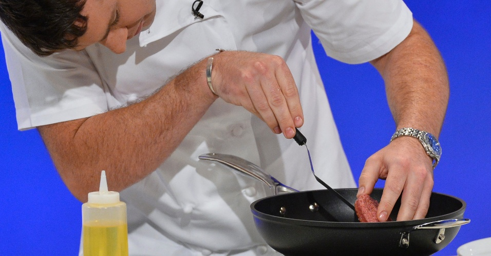 5.ago.2013 - O cozinheiro Richard McGeown frita o primeiro hamburguer produzido em laboratório em um evento nesta segunda-feira (5) em Londres, na Inglaterra. As pequenas tiras de carne produzidas a partir de células-tronco de bois são juntadas em pequenos montes e, depois, congeladas até atingir uma quantidade suficiente para serem compactadas na forma de um hambúrguer