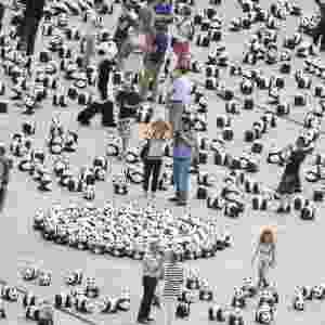 5.ago.2013 - Pessoas caminham entre 1.600 figuras de panda espalhados pela organização de defesa do meio-ambiente WWF (World Wildlife Fund) na frente da principal estação ferroviária de Berlim, na Alemanha, nesta segunda-feira (5). A WWF celebra seus 50 anos de existência chamando a atenção para espécies ameaçadas de extinção - Hannibal Hanschke/EFE