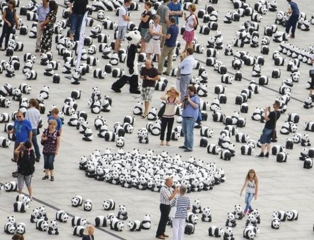 5.ago.2013 - Pessoas caminham entre 1.600 figuras de panda espalhados pela organização de defesa do meio-ambiente WWF (World Wildlife Fund) na frente da principal estação ferroviária de Berlim, na Alemanha, nesta segunda-feira (5). A WWF celebra seus 50 anos de existência chamando a atenção para espécies ameaçadas de extinção