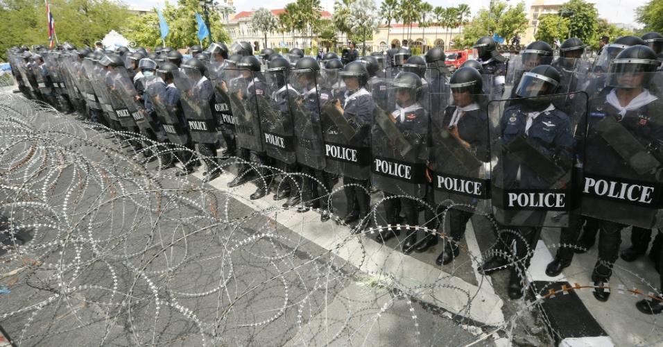 5.ago.2013 - Tropa de Choque da polícia tailandesa forma barricada em frente à sede do governo durante protesto em Bancoc, na Tailândia