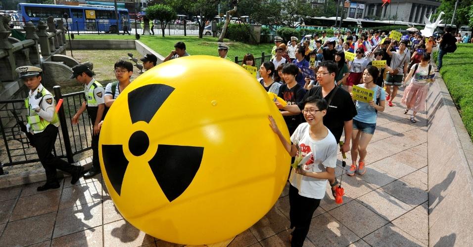 6.ago.2013 - Ativistas sul-coreanos marcham acompanhados de balão com o símbolo de alerta radioativo em protesto contra energia nuclear em Seul (Coreia do Sul) nesta terça-feira (6), quando completa-se 68 anos da explosão da bomba atômica em Hiroshima