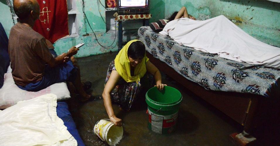 6.ago.2013 - Indiana remove água de dentro da casa inundada após tempestade em Amritsar, extremo norte da Índia, nesta terça-feira (6). As chuvas de monção atingem o país de junho a setembro e representam 80% da precipitação ao longo do ano