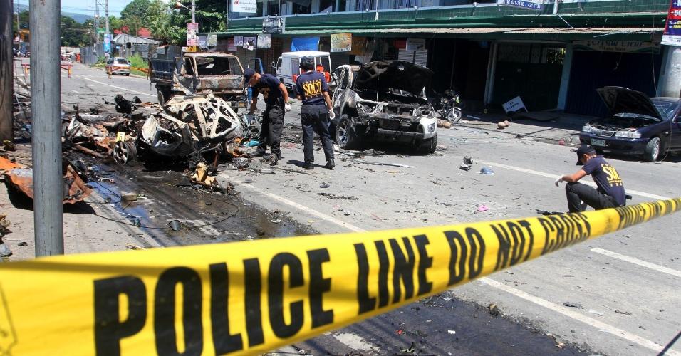 6.ago.2013 - Investigadores fazem inspeção em carro destruído, nesta terça-feira (6), um dia depois que uma explosão de bomba em Cotabato, no sul das Filipinas, causou a morte de oito pessoas