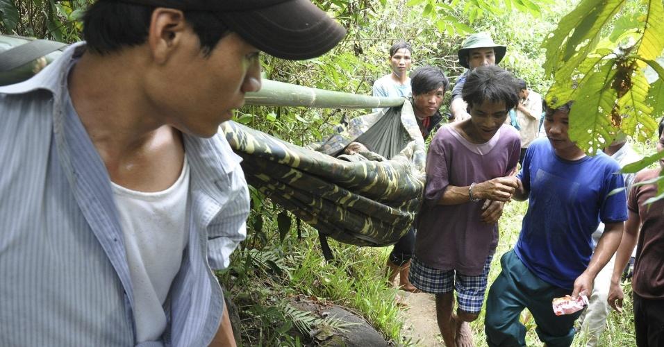 7.ago.2013 - Ho Van Lang (de bermuda quadriculada) e seu pai, Ho Van Than (deitado na rede), são retirados de floresta por autoridades vietnamitas