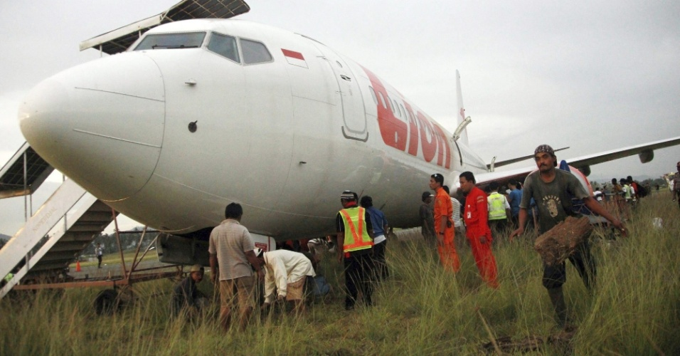 8.ago.2013 - Funcionários do Comitê Nacional de Segurança de Transporte inspecionam avião da companhia Lion Air, que patinou na pista do aeroporto internacional de Gorontalo (Indonésia)