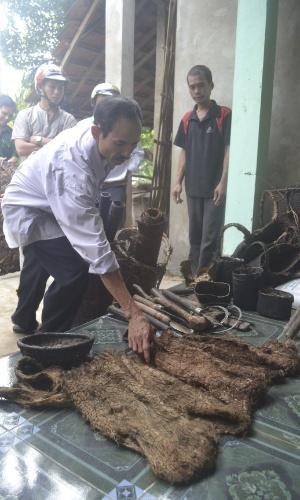 8.ago.2013 - Homem observa camisas feitas com casca de árvore e que eram vestidas por Ho Van Thanh e seu filho, Ho Van Lang, durante os 42 anos que os dois viveram na floresta