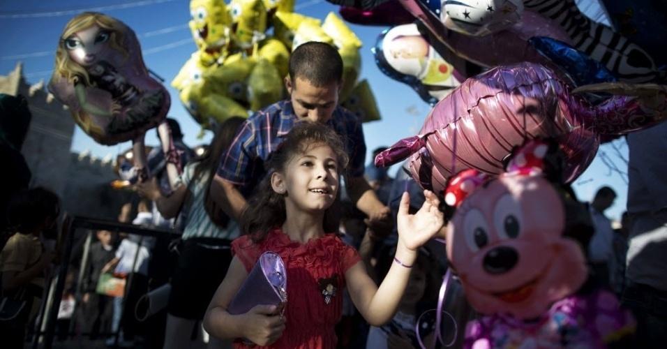 8.ago.2013 - Menina palestina olha balões à venda no Portão de Damasco, entrada da cidade antiga de Jerusalém, nesta quinta-feira (8). Milhares de palestinos se dirigiram ao local pra as orações na mesquita Al-Aqsa no primeiro dia do Eid Al-Fitr, feriado que marca o fim do mês sagrado do Ramadã