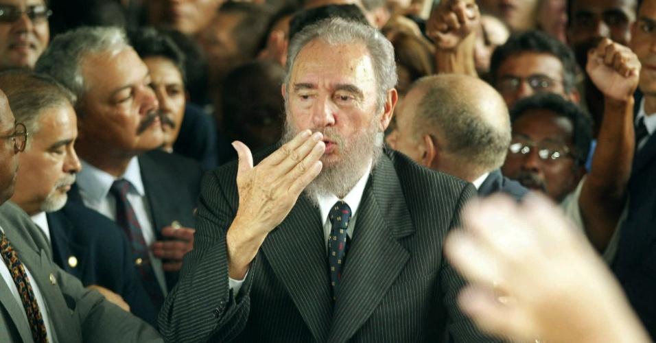 """12.ago.2013 - O ex-presidente cubano Fidel Castro solta beijos na saída do Ministério da Educação, em Brasília, em 2003, respondendo a saudações de curiosos e estudantes, que gritavam """"Cuba Sim, Yankes Não, Viva Fidel e a Revolução"""". Ele compareceu à posse do então ministro da Educação, Cristóvam Buarque"""