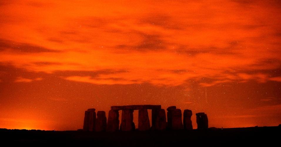 """13.ago.2013 - Em imagem utilizando técnica de longa exposição - em que o obturador da câmera permanece aberto por longos períodos, registrando objetos com baixa luminosidade, meteoro risca o céu por detrás do monumento de Stonehenge, no sul da Inglaterra, na madrugada desta terça-feira (13). A chuva de meteoros das Perseidas ocorre todo ano, geralmente em agosto, quando a Terra passa por um jato de """"destroços"""" deixados pelo cometa Swift-Tuttle em seu trajeto ao redor do sol"""
