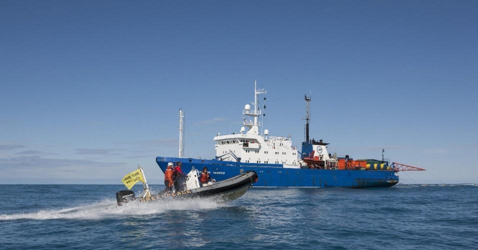 """13.ago.2013 - Lancha com ativistas do Greenpeace se aproxima do """"Akademic Lazarev"""" (ao fundo), barco da petroleira Rosneft que faz pesquisa sísmica no mar de Barents, no Ártico. A ONG protesta conta a exploração petrolífera e os testes, que são perigosos para os mamíferos da região, pois o sinal interfere nos sons emitidos pelos animais"""