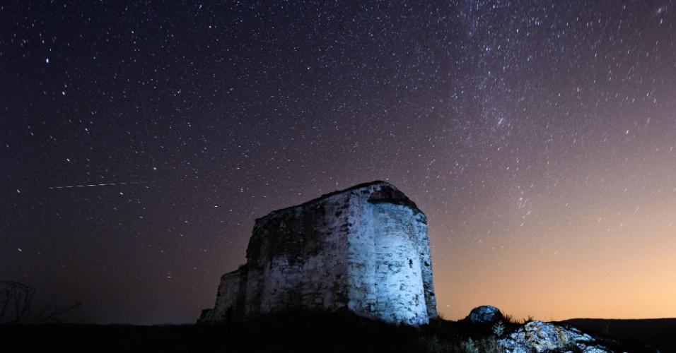 13.ago.2013 - Meteoro cruza o céu sobre a igreja medieval St. Ioan, no vilarejo de Potsurnentsi, na Bulgária, em registro de longa exposição