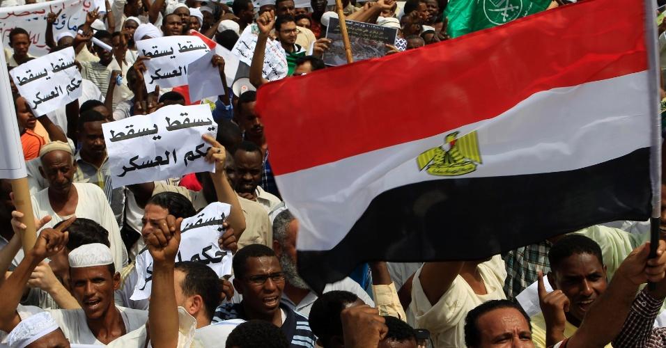16.ago.2013 - Apoiadores do presidente deposto do Egito, Mohamed Mursi, gritam palavras de ordem e erguem bandeiras do Egito durante protesto contra o massacre praticado pelo Exército egípcio contra defensores do ex-mandatário. A manifestação aconteceu em Khartoum, no Sudão, após as orações de sexta-feira (16)