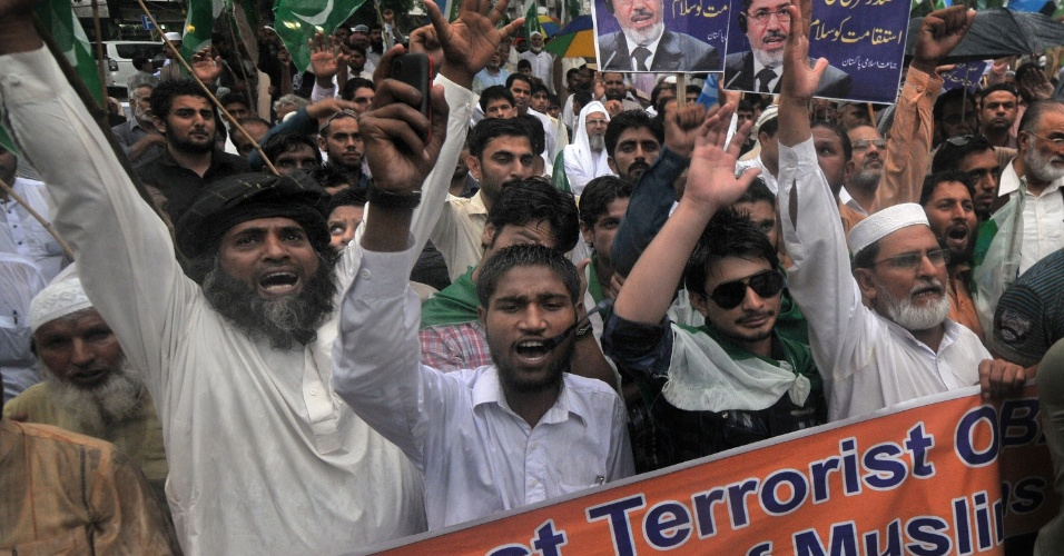 16.ago.2013 - Ativistas de vários partidos políticos, incluindo o Jamaat-e-Islami, gritam palavras de ordem durante protesto em apoio aos presidente deposto do Egito, Mohamed Mursi, nesta sexta-feira (16), em Karachi, no Paquistão. Milhares de pessoas foram às ruas para condenar o Exército egípcio pelo massacre ocorrido no país
