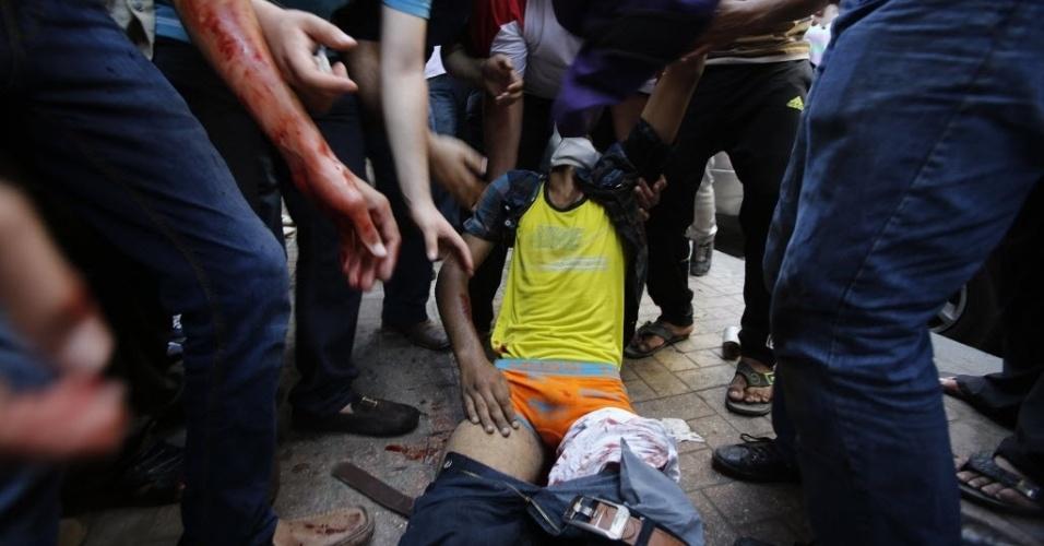 16.ago.2013 - Egípcios levam homem ferido durante confrontos no Cairo nesta sexta-feira (16). Um protesto realizado por partidários do presidente deposto do Egito Mohamed Mursi acabou em choque com a polícia. O governo egípcio contabiliza dezenas de mortes