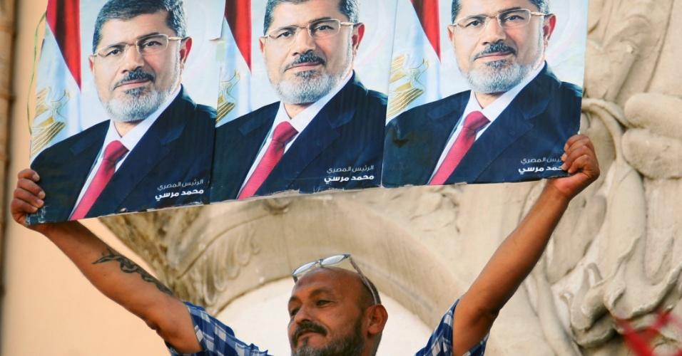 16.ago.2013 - Homem segura cartazes com o rosto do presidente egípcio deposto, Mohamed Mursi, durante protesto contra o massacre protagonizado pelo Exército contra os defensores do ex-mandatário, nesta sexta-feira (16), em Túnis, na Tunísia
