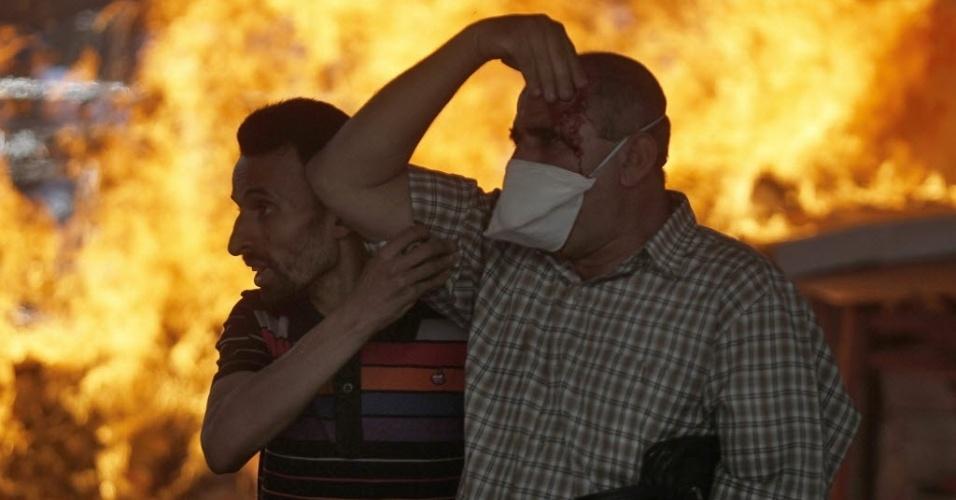 16.ago.2013 - Manifestante ferido recebe ajuda de colega durante protesto em frente ao centro policial Azbkya, no Cairo, nesta sexta-feira (16). O governo do Egito contabiliza dezenas de mortes durante os confrontos de hoje pelo país