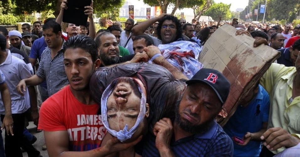 16.ago.2013 - Manifestantes favoráveis ao ex-presidente deposto do Egito Mohamed Morsi carregam corpo de colega baleado em confronto durante marcha por ruas do Cairo nesta sexta-feira (16). A Irmandade Muçulmana do Egito fez uma convocação nacional para uma
