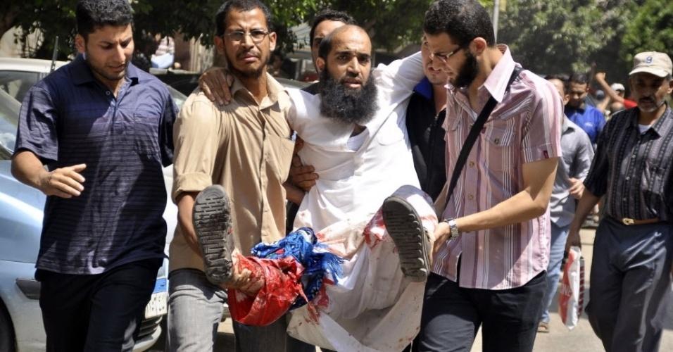 16.ago.2013 - Manifestantes favoráveis ao ex-presidente deposto do Egito Mohamed Morsi carregam pessoa baleada em confronto durante marcha por ruas do Cairo nesta sexta-feira (16). A Irmandade Muçulmana do Egito fez uma convocação nacional para uma
