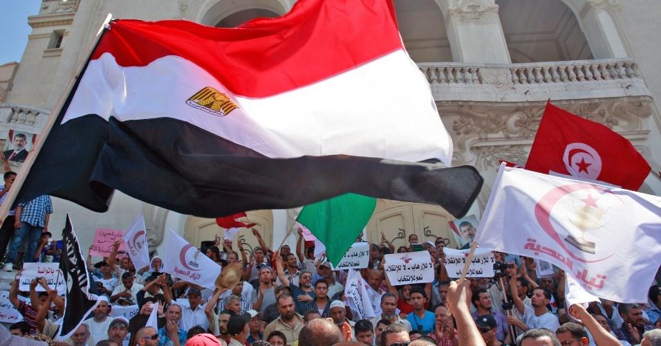 16.ago.2013 - Manifestantes gritam palavras de ordem e levantam bandeiras de vários países áreabes, inclusive a egípcia, durante protesto em Túnis, na Tunísia, nesta terça-feira (16) para mostrar apoio ao presidente egípcio deposto, Mohamed Mursi. França e Grã-Bretanha chamaram a atenção da Europa para que seja enviada uma mensagem forte sobre o agravamento da crise no Egito, pedindo para que a União Europeia reveja as suas relações com Cairo