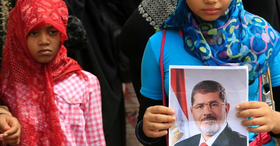 16.ago.2013 - Meninas sudanesas seguram cartaz com a foto do presidente deposto do Egito, Mohamed Mursi, durante protesto contra o massacre praticado pelo Exército egípcio contra defensores do ex-mandatário. A manifestação aconteceu em Khartoum, no Sudão, após as orações de sexta-feira (16)