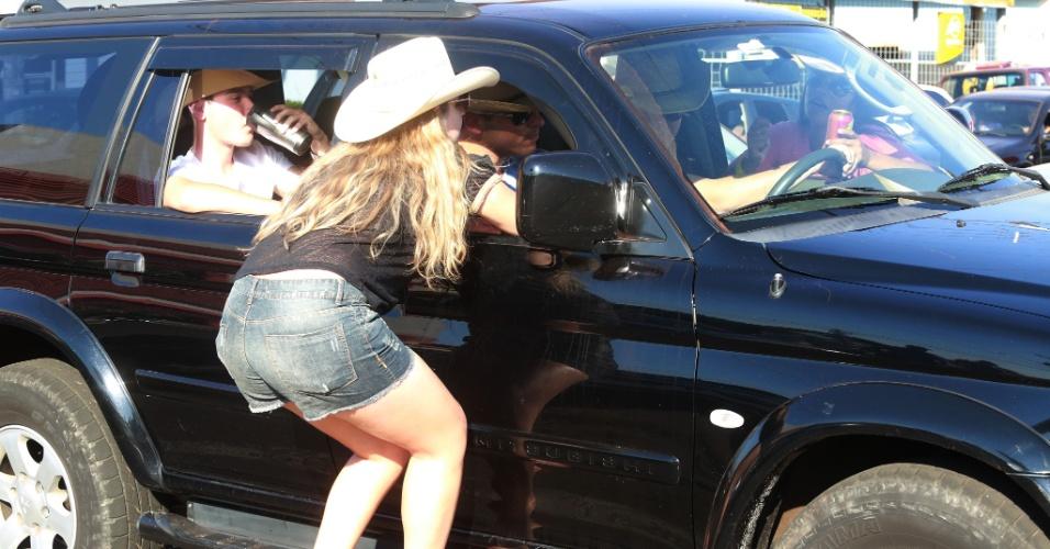 """17.ago.2013 - Mulher pega """"carona"""" em caminhonete que circula pela avenida 43, em Barretos (SP), onde acontece a 58ª edição da Festa do Peão. Neste sábado (17) à tarde, os frequentadores fazem o """"esquenta"""""""