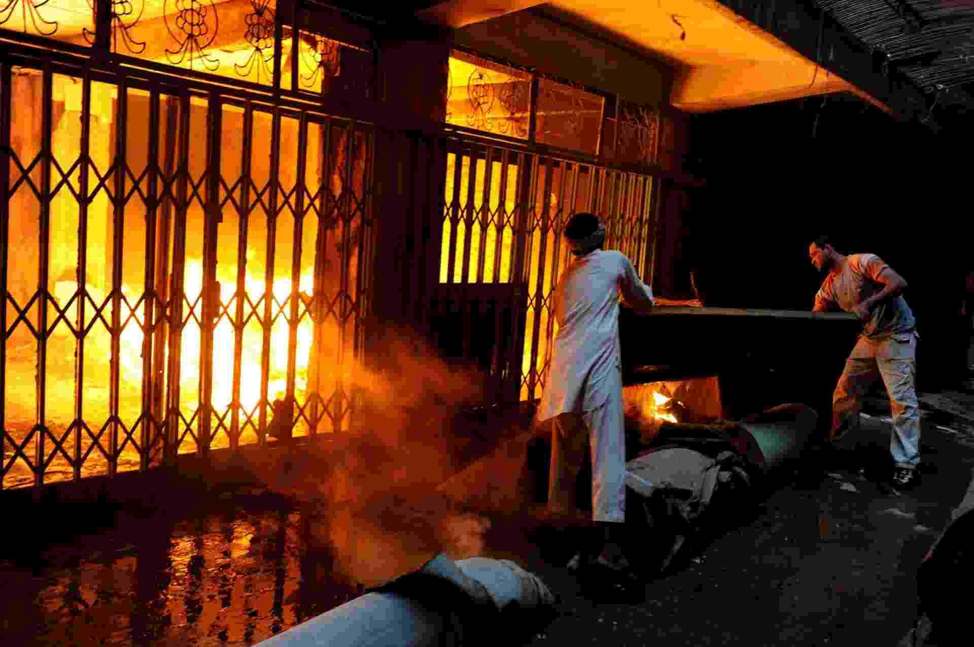 17.ago.2013 - Proprietários tentam, em vão, conter incêndio que destrói lojas de ouro e carpetes em mercado de Mazar-i Sharif, no Afeganistão. - Farshad Usyan/AFP