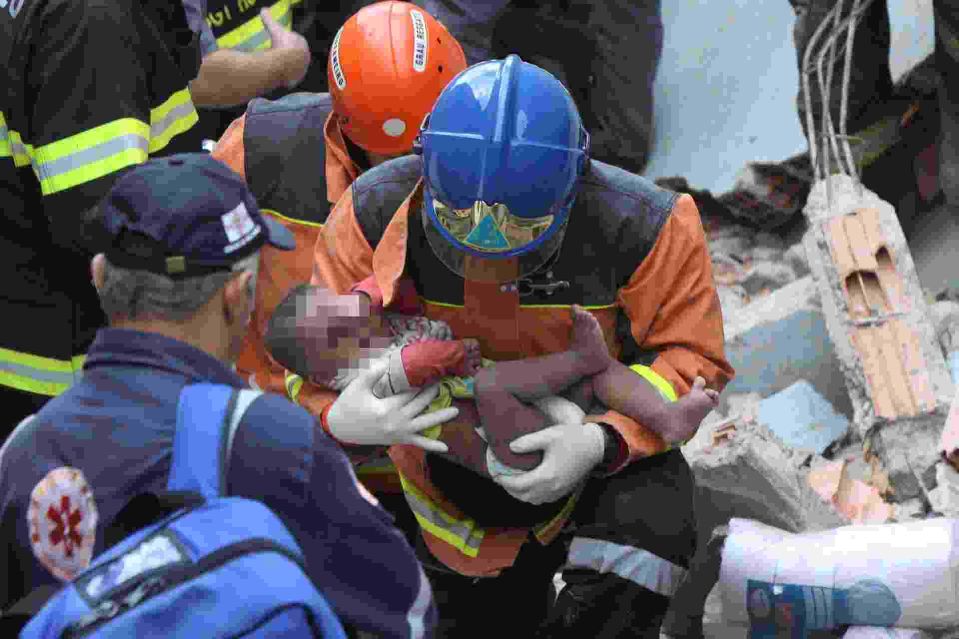 19.ago.2013 - Criança vítima de explosão de gás em uma casa na Brasilândia, zona norte de São Paulo, é resgatada dos escombros por equipe do Corpo de Bombeiros nesta segunda-feira. Segundo a corporação, ao menos quatro pessoas estavam dentro da residência no momento do acidente. Às 12h45 a última delas foi resgatada. A casa ficou completamente destruída. Ao menos 13 carros dos bombeiros, além do helicóptero Águia, da Polícia Militar, foram enviados para o local da ocorrência - Marcos Bezerra/Futura Press