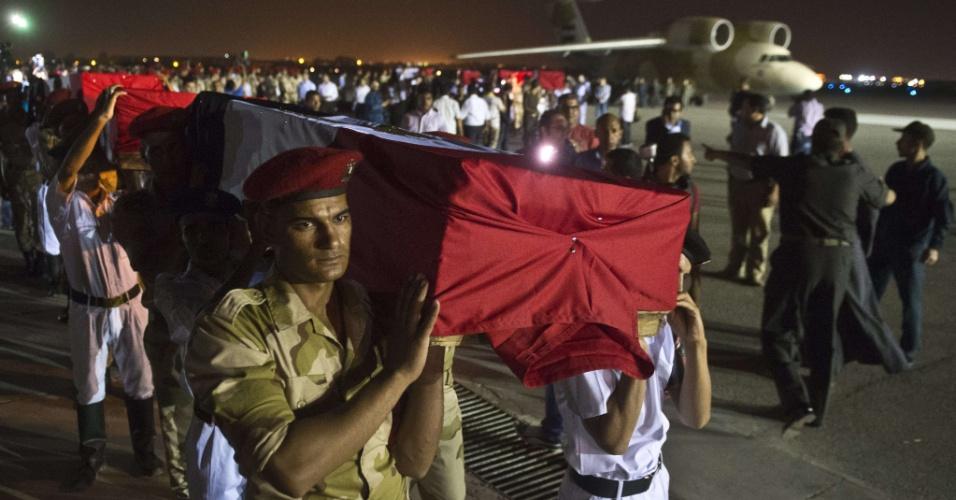 19.ago.2013 -Exército e policiais egípcios carregam caixões cobertos com bandeiras nacionais na base militar de Almaza, no Cairo, Egito. Grupos islamitas armados atacaram nesta segunda-feira dois micro-ônibus da polícia com foguetes, matando 25 policiais que iam para Rafah. Esse ataque, o mais mortífero contra as forças de ordem em décadas, eleva para 102 o número de policiais mortos em cinco dias