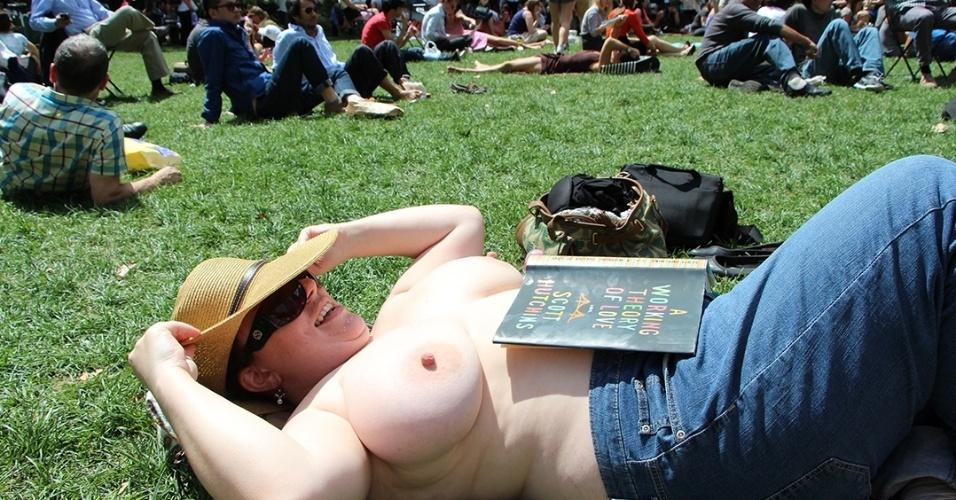 """Integrante do """"The Outdoor Co-ed Topless Pulp Fiction Aprecciation Society"""" participa de leitura e aproveita para tomar sol no Bryant Park, em Nova York"""