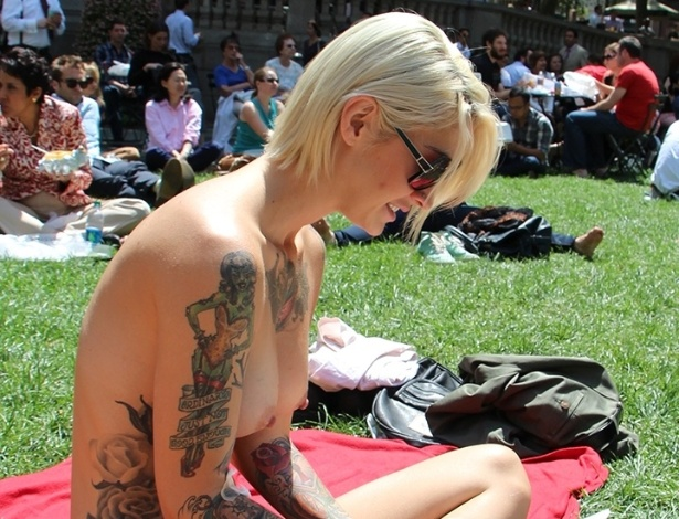"À vontade e nada incomodada por estar sem blusa, integrante do ""The Outdoor Co-ed Topless Pulp Fiction Aprecciation Society"" participa de leitura no Bryant Park, em Nova York"