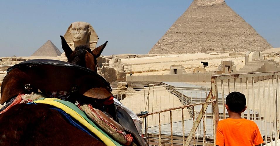 21.ago.2013 - Em imagem de 3 agosto, garoto egípcio aguarda por turistas em frente à esfinge e às grandes pirâmides de Gizé, a sudoeste do Cairo, no Egito. O turismo no país foi duramente atingido diante da crise política instaurada desde a deposição do ditador Hosni Mubarak, em 2012, e agravada com o golpe militar sobre o primeiro presidente eleito do país, Mohammed Mursi, que culminou na última semana com a morte de centenas de manifestantes a favor do mandatário deposto. Nesta quarta-feira (21), as pirâmides permaneciam oficialmente fechadas