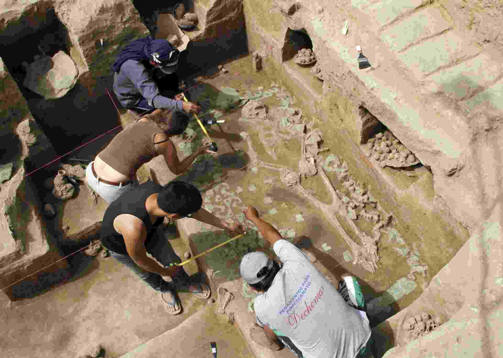 22.ago.2013 - Trabalhadores removem poeira e detritos de uma câmara funerária pré-hispânica achada no mês passado na província de Chepén, na região La Libertad, no Norte do Peru. A ossada de uma sacerdotisa da cultura Moche (entre 200 d.C. e 700 d.C.) foi a oitava descoberta do tipo em um período de duas décadas, confirmando que as mulheres governavam a região há 1.200 anos - Douglas Suarez/AFP